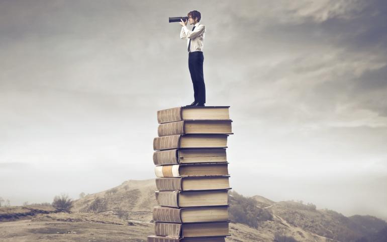 Man-Standing-on-Books