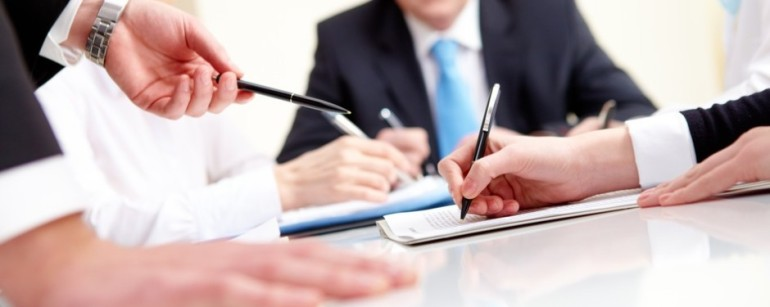 Close-up of business partners hands during planning in working environment