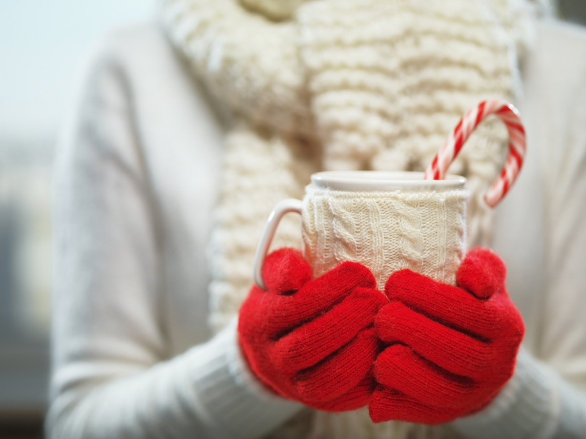 Woman holding winter cup close up on light background. Woman han